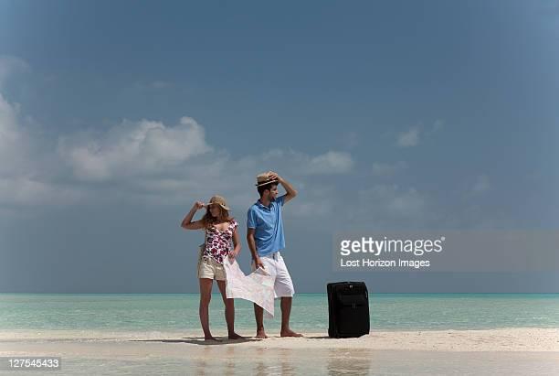 Perte de couple tenant la carte sur la plage