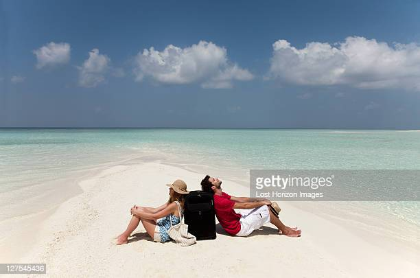 Lost couple sitting together on beach