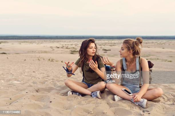 lost friends talking while sitting in desert - female friendship stock pictures, royalty-free photos & images