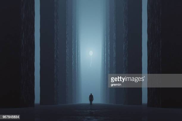 lost man walking in dark foggy street towards illuminated balloon - ominous stock pictures, royalty-free photos & images