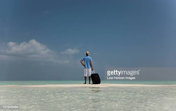 Lost man with luggage on beach