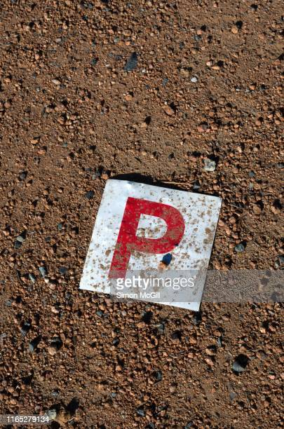 lost p plate laying on the dirt shoulder of a road - letter p stock pictures, royalty-free photos & images