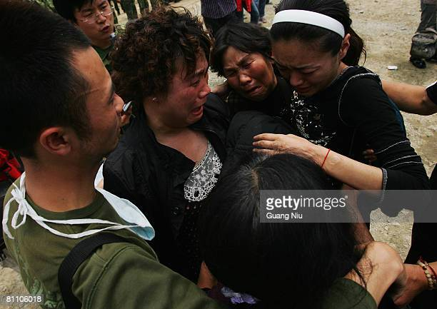 Lost relatives embrace after they meet at a landing point at Zipingba dam on May 16 2008 between Wenchuan and Dujiangyan Sichuan Province China A...