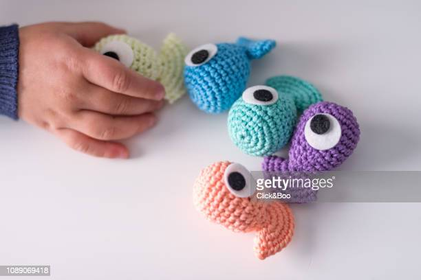 A lot of crocheted funny little fishes on a white chair (handmade)