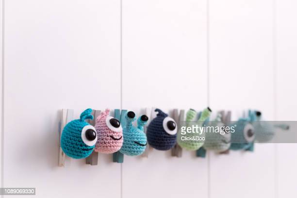 A lot of crocheted funny little monsters glued to a clothespin on a white wall (handmade)