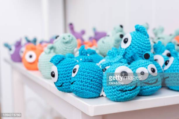 a lot of crocheted funny little monsters on a white chair (handmade) - click&boo fotografías e imágenes de stock