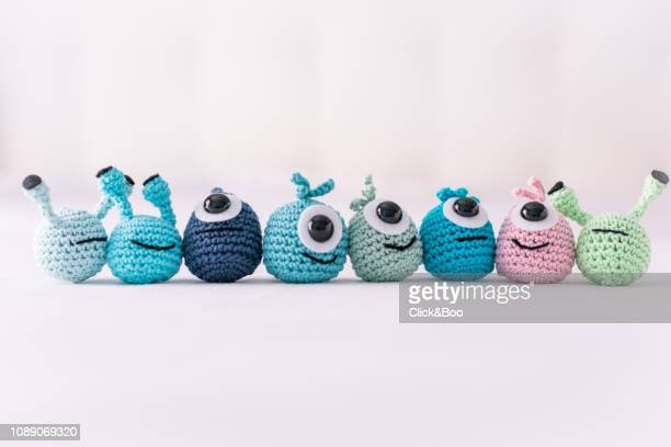 A lot of crocheted funny little monsters on a white surface (handmade)