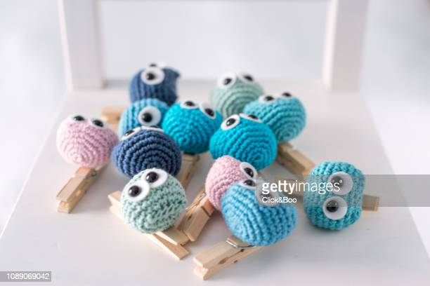A lot of crocheted funny little owls on a white chair (handmade)