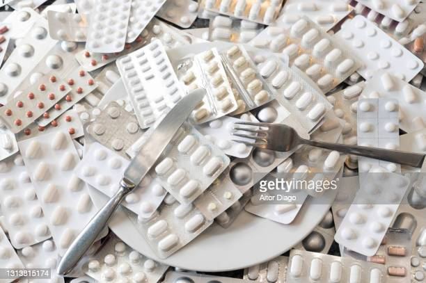a lot of encapsulated pills on a plate with fork and knife ready to be eaten. humor. there is a large number of pills on a table. humor - generic drug stock pictures, royalty-free photos & images