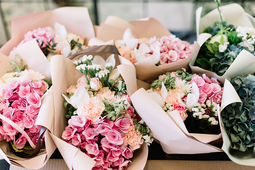 A lot of flower bouquets at the florist shop on the table made of hydrangea, roses, peonies, eustoma in pink and sea green colors 1159802579