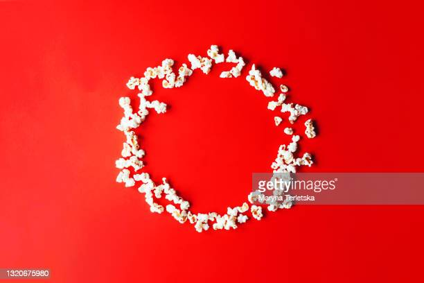 a lot of popcorn on a red background. - film screening stock pictures, royalty-free photos & images