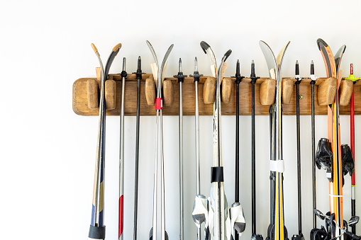 Lot of ski hanged on customized wooden wall mount at garage for seasonal storage. Extreme winter sport equipment handling at home warehouse 1075709410