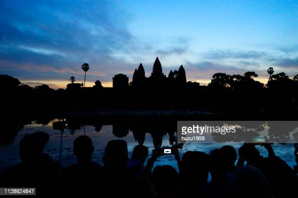 A lot of tourists take photos of dawn of Angkor Wat