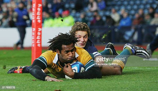 Lote Tuqiri of Australia scores the first try under the tackle of Chris Cusiter of Scotland during the International Friendly match between Scotland...