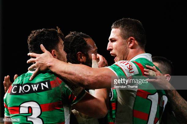 Lote Tuqiri of the Rabbitohs celebrates with team mates Dylan Walker and Sam Burgess after scoring a try during the round 19 NRL match between the...