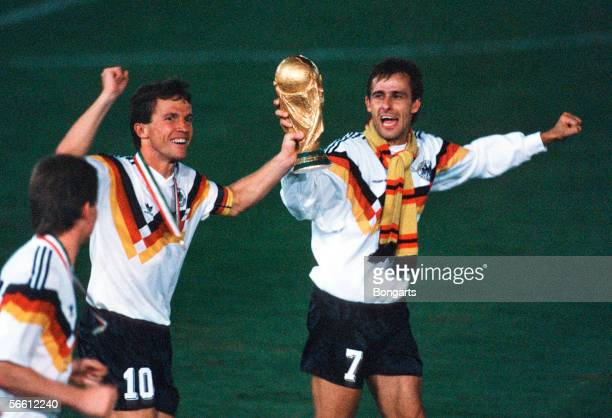 Lothar Matthaeus and Pierre Littbarski of Germany celebrates with the trophy after winning the World Cup final match between Argentina and Germany at...