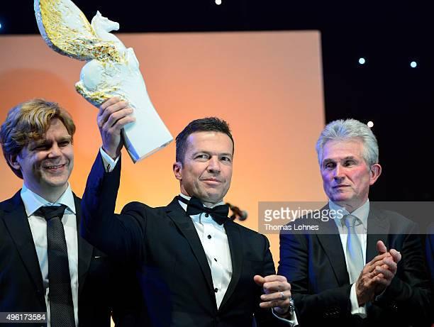 Lothar Matthaeus receives the PEGASOS 'Legend of Sports' award while his laudatory Jupp Heynckes and moderator Michael Steinbrecher stands behind him...