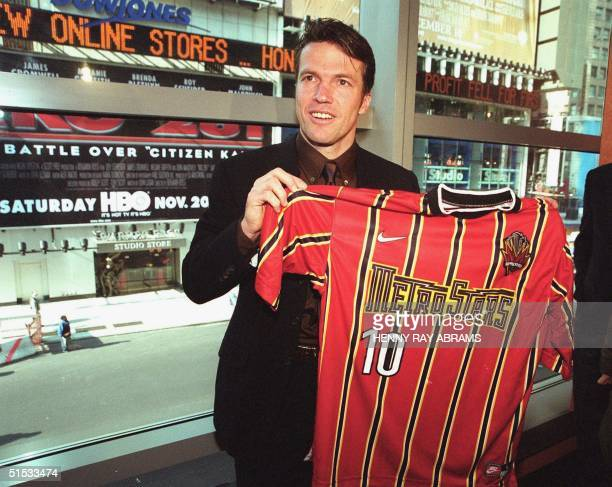 Lothar Matthaus the 198999 German Footballer of the Year stands in front of a window overlooking Times Square in New York City after the press...