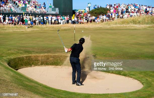 Northern Irish golfer Rory McIlroy chips out of the 19th green bunker.