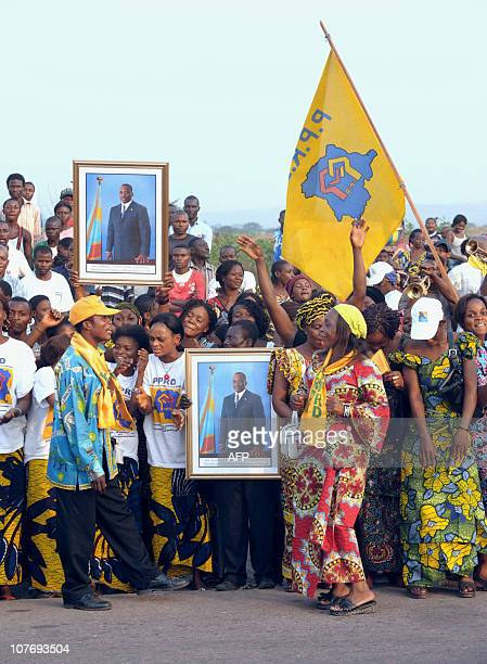 Lots of Congolese people wait to see the arrival of King Albert II and Queen Paola with portraits of their President Joseph Kabila at Kinshasa...