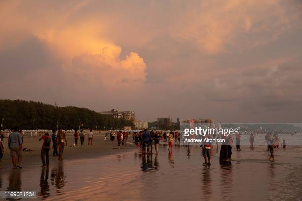 Lots of people on the busy Laboni Beach at sunset in Cox Bazar Chittagong Division Bangladesh Asia Beachfront buildings of the city can be seen in...