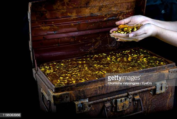 lots of stacking gold coin in lady hand and treasure chest at black background - 宝箱 ストックフォトと画像