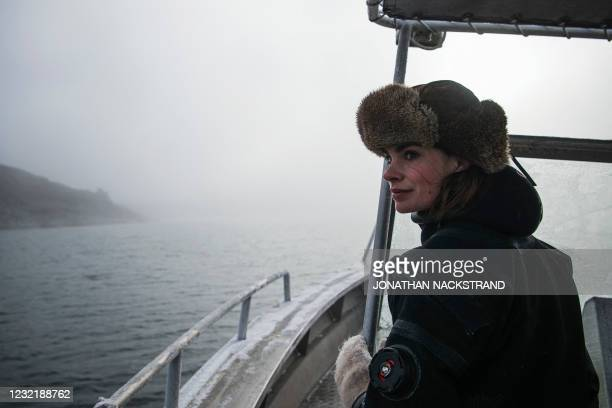 Lotta Klemming, a professional oyster diver, helps steering the boat through frozen waters before a dive, near her familys company in Grebbestad in...
