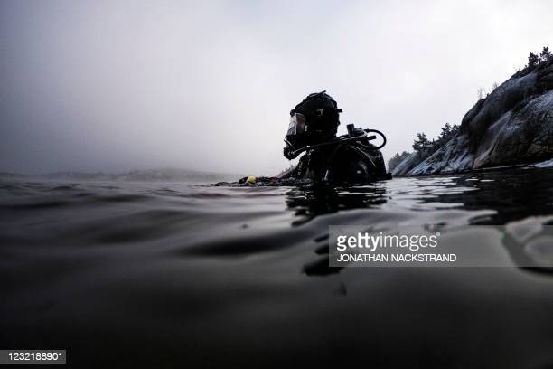 Lotta Klemming, a professional oyster diver, reemerges from the water while collecting oysters during a dive, near her familys company in Grebbestad...