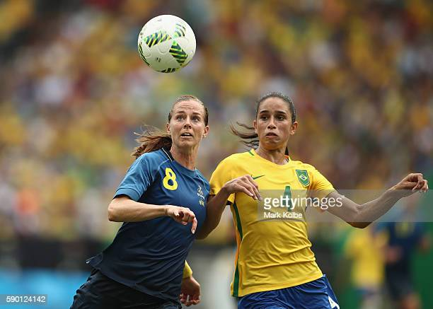 Lotta Schelin of Sweden and Rafaelle of Brazil compete for the ball during the Women's Football Semi Final between Brazil and Sweden on Day 11 of the...