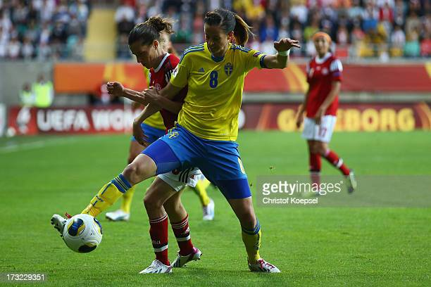 Lotta Schelin of Sweden challenges Johanna Rasmussen of Denmark during the UEFA Women's EURO 2013 Group A match between Sweden and Denmark at Gamla...