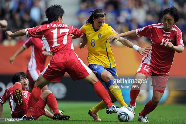 Lotta Schelin of Sweden is challenged by Song Jong Sun Ri Un Hyang and Jon Myong Hwa of Korea DPR during the FIFA Women's World Cup Group C match...