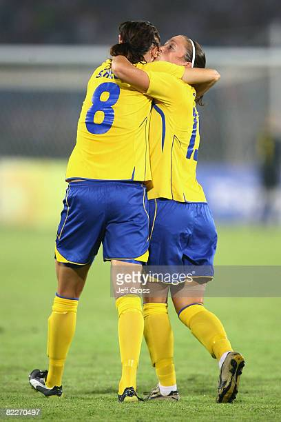 Lotta Schelin of Sweden is congratulated by teammate Therese Sjogran after scoring the opening goal during the Women's First Round Group E match...