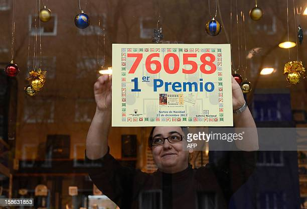 A lottery seller who sold the winning ticket of Spain's Christmas lottery hangs a placard reading the winning number 76058 on her shop windowcase in...
