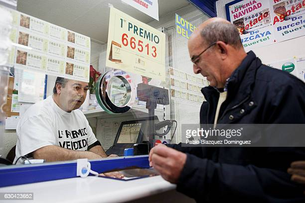 Lottery shop owner Agustin Ramos sells 'primitiva' lottery to Agustin Fuentes who got three first prize winning tickets of Spain's Christmas lottery...