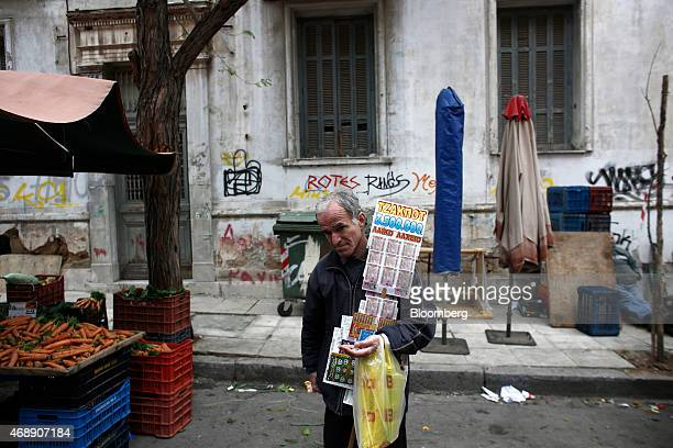 A lottery ticket seller counts his euro coins while waiting for customers at a street market in Athens Greece on Wednesday April 8 2015 Russian...