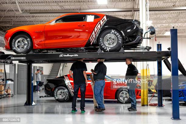 Lottery winner Kevin Mitchell center views the undercarriage of his new General Motors Co Chevrolet COPO Camaro inside the company's build center in...