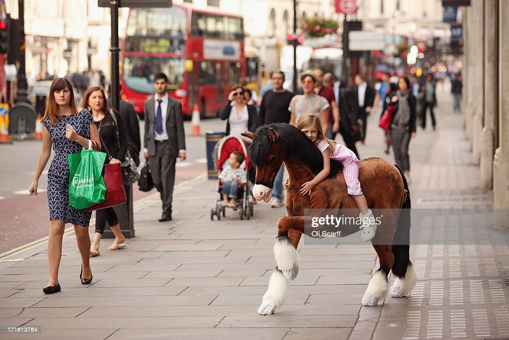 Lottie, aged 5, rides a Clydesdale Prancing Pony outside Hamleys toy shop on June 27, 2013 in London, England. The soft toy pony retails for 850 GBP and is included in Hamleys' predictions for the top selling toys for Christmas 2013.