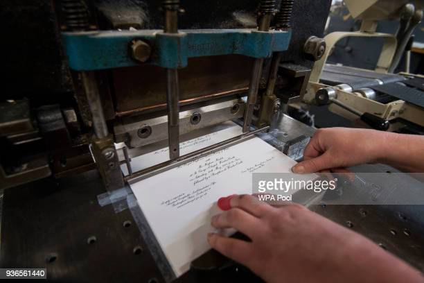 Lottie Small uses the die stamping press at the workshop of Barnard and Westwood who are printing the invitations for Prince Harry and Meghan...
