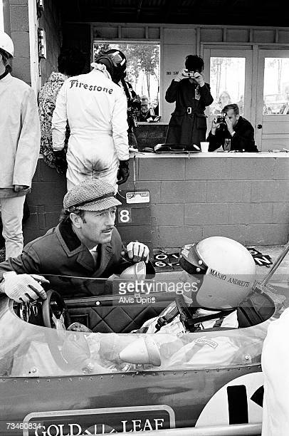 Lotus Team owner Colin Chapman talks with Mario Andretti during practice for his first Formula One Grand Prix race in which he captured the pole...