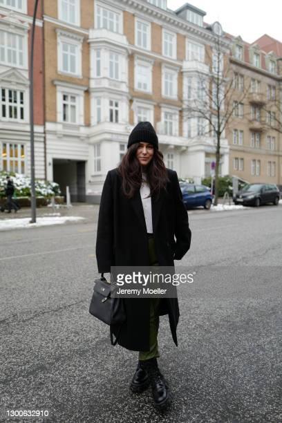 Lou Beyer wearing black COS coat, Allude white sweater, black Prada boots, black Hermes Kelly 28 bag, black Unio Hamburg hat and green Oakwood pants...