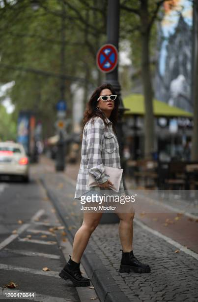 Lou Beyer wearing Hermes clutch Prada boots Baum Pferdgarten shirt Agolde short Edited top and Celine shades on August 14 2020 in Cologne Germany
