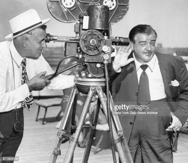 Lou Costello holds ear to camera aboard the Queen Elizabeth