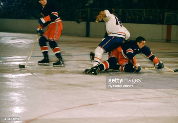 Lou Fontinato of the New York Rangers goes for the puck as he is defended by Dollard St Laurent of the Montreal Canadiens while Harry Howell of the...