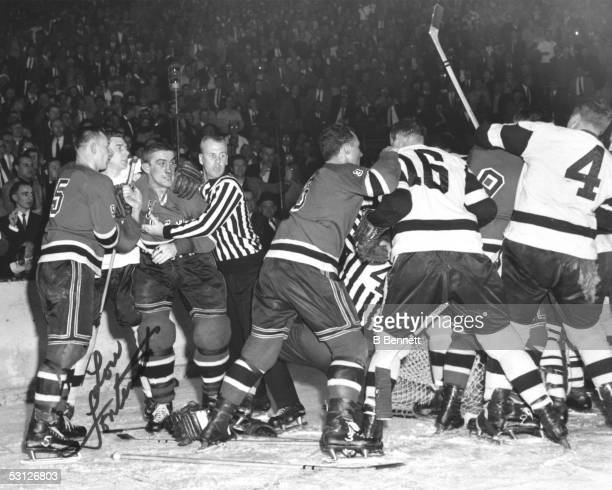 Lou Fontinato of the New York Rangers is held back after he and Gordie Howe of the Detroit Red Wings incite a brawl during their game in the 1950's...