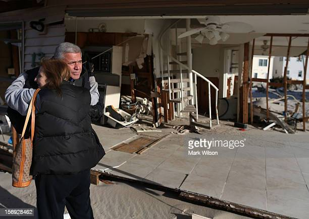 Lou Friedella is in tears as he gets a hug from his wife Susan in front of their beach house that was damaged by Superstorm Sandy on November 25,...