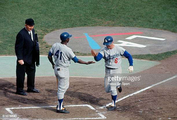 Lou Johnson of the Dodgers greets Ron Fairly at home base during the 1965 World Series at the Metropolitan Stadium in Bloomington MN in October 1965