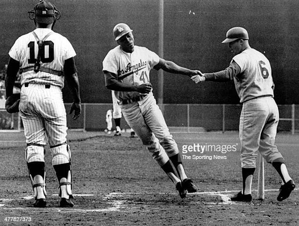 Lou Johnson of the Los Angeles Dodgers is congratulated by Ron Fairly after Johnson hit a home run in the fourth inning of Game Seven of the 1965...