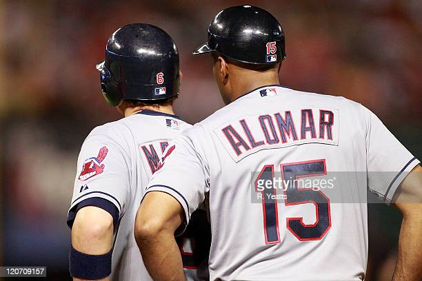 Lou Marson of the Cleveland Indians and first base coach Sandy Alomar Jr #15 talk during the game against the Texas Rangers at Rangers Ballpark in...