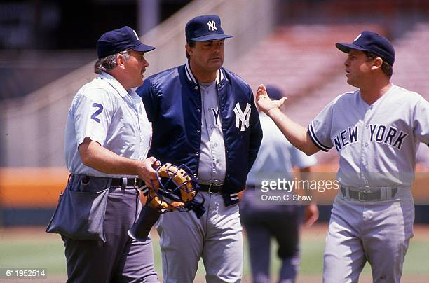 Lou Piniella manager of the New Yourk Yankees circa 1987 confers with ump and Tommy John in a game against the California Angels at the Big A in...