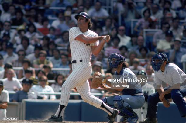 Lou Piniella of the New York Yankees watches the flight of the ball as he follows through on his swing during a 1977 season game at Yankee Stadium in...